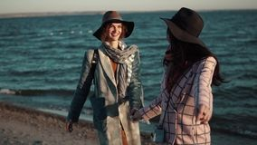 Carefree girlfriend walk along the beach at sunset and enjoy the warm autumn evening. two girls in autumn coat have fun. Young woman in elegant coat walks on the stock footage