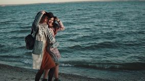 Carefree girlfriend walk along the beach at sunset and enjoy the warm autumn evening. two girls in autumn coat have fun. Young woman in elegant coat walks on the stock video footage