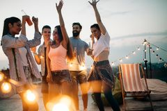 Carefree group of happy friends enjoying party on rooftop terrace stock image