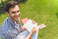 Carefree guy doing homework in park. I like studying. Joyful male student is sitting on grass and making notes. He is looking at camera and smiling. Man is Royalty Free Stock Photo
