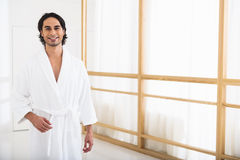 Carefree guy enjoying his vacation. Good morning. Happy young man is standing in bathrobe at home. He is looking at camera and smiling Royalty Free Stock Photo