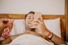 Carefree guy enjoying new day.Handsome young man in bed typing on cell phone, sending text message or dialing number.  royalty free stock photos