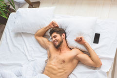 Carefree guy enjoying new day. I am happy to wake up in the morning. Joyful young man is lying in bed near smartphone and stretching his arms. He is laughing Stock Image