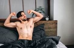 Carefree guy enjoying new day. Sexy, happy bearded man in bed.  Royalty Free Stock Photography