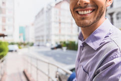 Carefree guy laughing with happiness. Close up of happy young man smiling with joy. He is standing on street Royalty Free Stock Photography