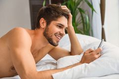 Carefree guy messaging on mobile phone at home. Joyful young man is using smartphone and laughing. He is lying in bed after sleep Royalty Free Stock Photography