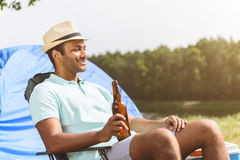 Carefree guy relaxing in camp. Happy young man is enjoying the nature. He is sitting on folding chair and smiling. Man is drinking beer and smiling Royalty Free Stock Photos