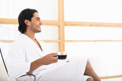 Carefree guy relaxing with hot drink. Happy young man is drinking coffee in morning. He is sitting on chair with relaxation and smiling. Man is wearing white Royalty Free Stock Photography