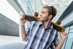 Carefree guy relaxing with skateboard. Happy young man is holding skate on his shoulders. He is standing and looking aside with interest Stock Photography
