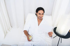 Carefree guy relaxing at wellness center. Happy young man is reading magazine and drinking lemonade at spa. He is lying on couch in bathrobe with relaxation. Man Royalty Free Stock Photography