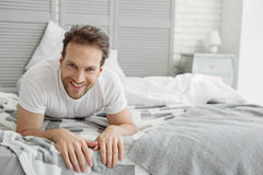 Carefree guy resting in bedroom. Portrait of happy man is lying and relaxing on bed. He is looking at camera and laughing Stock Photos