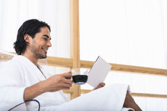 Carefree guy resting on vacation. Joyful young man is relaxing in morning. He is drinking coffee and reading book. Man is sitting in bathrobe and smiling Stock Images