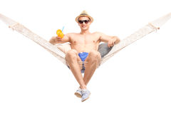 Carefree guy sitting in hammock and drinking a cocktail. Carefree young guy sitting in a comfortable hammock and drinking an orange cocktail isolated on white Stock Photo
