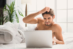 Carefree guy using computer in bedroom. Confident young man is typing on laptop and smiling. He is lying on bed with relaxation Royalty Free Stock Photography