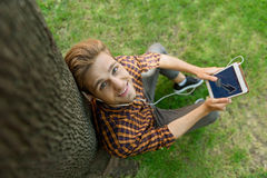 Carefree guy using technology in nature. Top view of joyful young man sending message on tablet. He is sitting near tree and relaxing with earphones. Man us Royalty Free Stock Photography