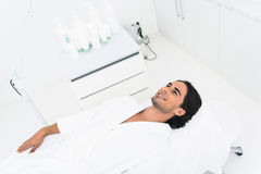 Carefree guy waiting for cosmetic treatment. Happy young man is lying on table in beautician office. He is smiling with anticipation Royalty Free Stock Photo