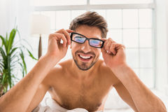 Carefree guy wakes up at home. Good morning. Happy young man is wearing eyeglasses after waking up. He is sitting in bed and laughing Royalty Free Stock Image
