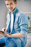Carefree guy. Young smiling man using touchpad Royalty Free Stock Image