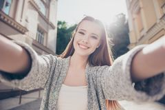 Carefree and happy, sunny mood. Cute young smiling girl is making selfie on a camera. She is wearing casual outfit stock image