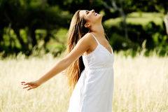 Carefree happy woman. Happy carefree vitality freedom girl stands with her hands outstretched embracing nature and a warm summer day Stock Photo