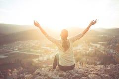 Carefree happy woman sitting on top of mountain edge cliff enjoying sun on her face raising hands in sunlight rays. Enjoying natur