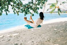 Carefree happy woman on swing on beautiful paradises beach stock images