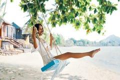 Carefree happy woman on swing on beautiful paradises beach stock photos