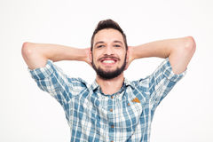 Carefree happy young bearded man with hands behind head Royalty Free Stock Images