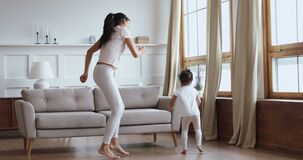 Carefree healthy mom and child daughter having fun dancing together
