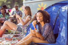 Carefree hipster blowing bubbles in tent. At a music festival Stock Photos