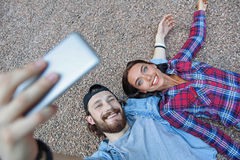 Carefree hipsters photographing themselves on smartphone Royalty Free Stock Photography