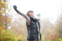 Carefree kvinna med Outstreched armar i höst Fotografering för Bildbyråer