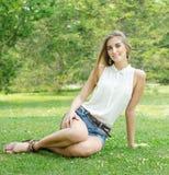 Carefree kvinna som sitter i ett grönt fält Royaltyfria Bilder