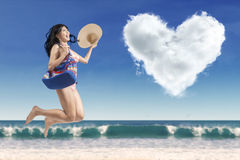 Carefree lady with a heart-shaped cloud. Portrait of carefree woman wearing swimwear, carrying handbag and jumping at beach with a heart-shaped cloud Stock Photo