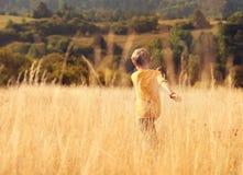 Carefree little boy run across high golden grass Stock Photography