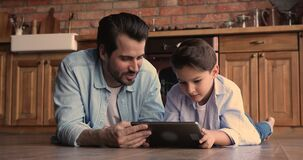 Little boy spend weekend with dad in kitchen with tablet