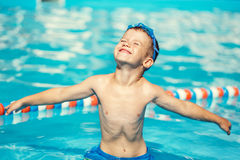 Carefree little caucasian boy spread arms in pool Royalty Free Stock Photography
