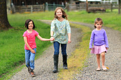Carefree little country girls. Three little country girls walking on a tractor road Stock Photos