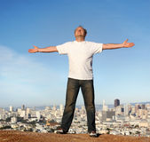 Carefree living. A man standing on a hill with a view of San Francisco, his arms raised Stock Images