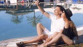 Carefree lovers resting near swimming pool. Couple on vacation, sunbathing, relaxing. Vacation, tourism, hooneymoon. Talk on the phone, smile, fast internet stock video