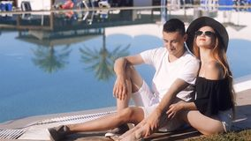 Carefree lovers resting near swimming pool. Girl in sunglasses and hat. Couple on vacation, sunbathing, relaxing. Beackground palm. S and pool. Vacation, tourism stock video