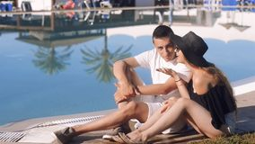Carefree lovers resting near swimming pool. Girl in sunglasses and hat. Couple on vacation, sunbathing, relaxing. Vacation, touris. M, hooneymoon.Talk on the stock video