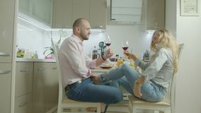 Happy couple toasting with red wine in kitchen