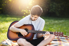 Carefree male with dark beard and trendy hairstyle learning to play guitar while sitting crossed legs at wrap. Young man playing m Stock Photography