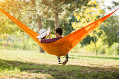 Carefree male and female in hammock from back Stock Photography