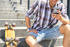 Carefree male skater entertaining outdoors. Happy young man is using smartphone and smiling. He is wearing earphones. Guy is sitting on steps near skate Royalty Free Stock Image