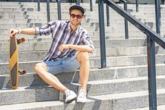 Carefree male skater sitting on stairs. Joyful young guy is listening to music and relaxing. He is sitting on steps and carrying skater. Man is looking at camera Royalty Free Stock Image