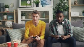 Carefree male students are playing video game on couch at home, pressing buttons on joystick concentrated on activity. Friendship, houses and modern technology stock video