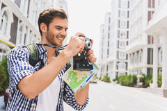 Carefree male tourist using camera in city Stock Images