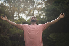 Carefree man with arms outstretched against trees. At park Royalty Free Stock Photo